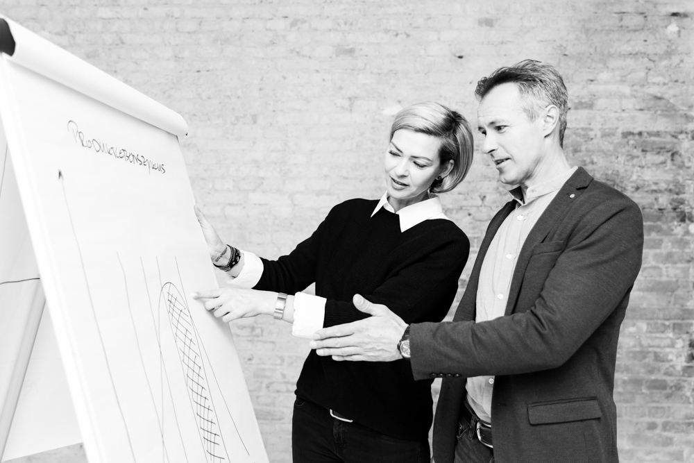 Coachingsituation am Flipchard mit Trainer und Klient für die Bebilderung einer Businesswebsite.