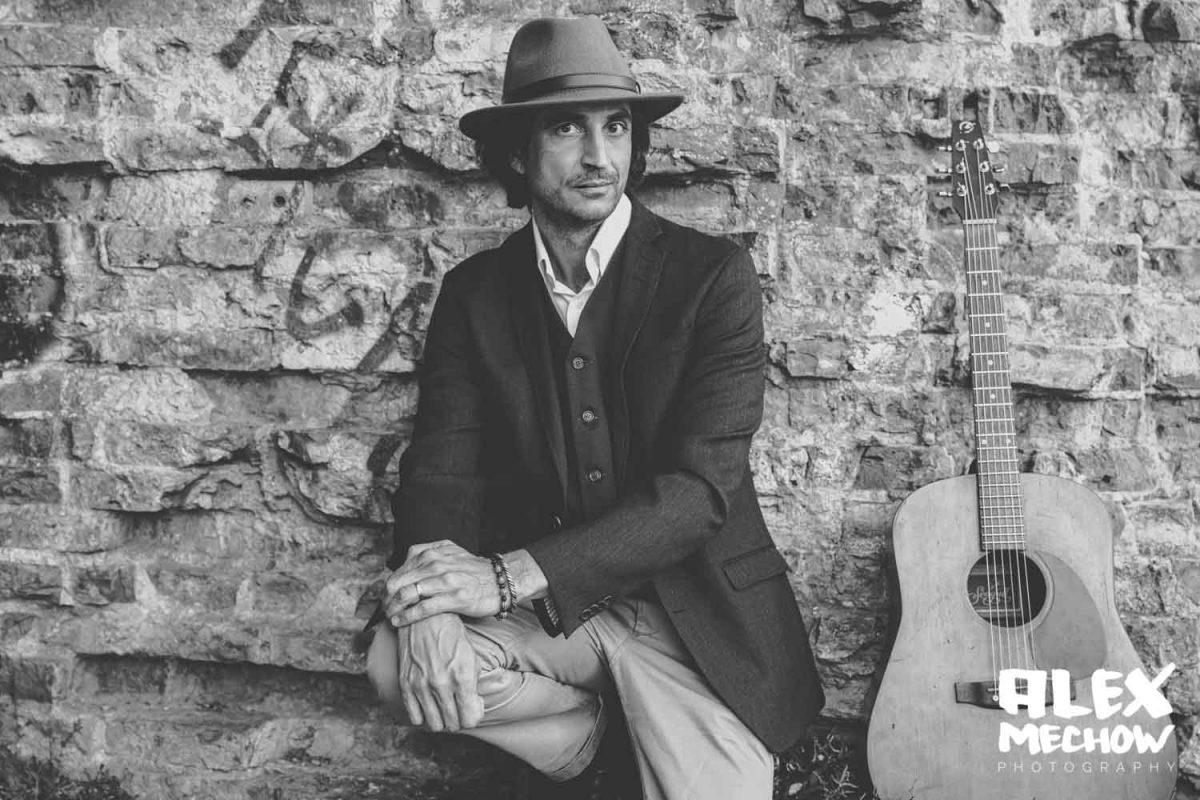 Stylischer Musiker mit Hut neben seiner Gitarre vor einer Steinwand in Berlin.