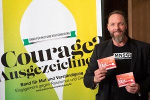 Der Berliner Fotograf Alexander Mechow mit seinem Piktogrammbuch für Migranten und ankommende Flüchtlinge.